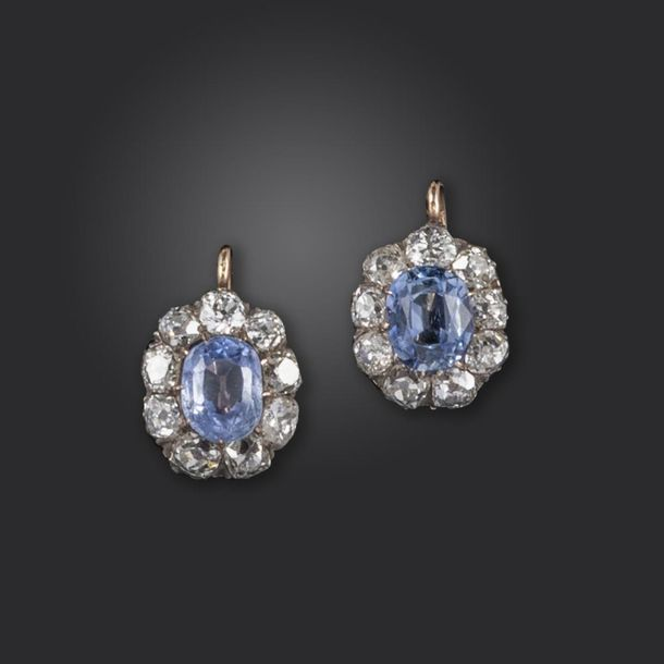 A pair of sapphire and diamond cluster earrings, the oval sapphires are each set…
