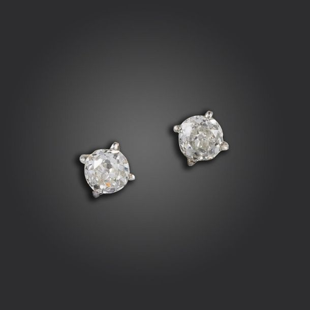 A pair of diamond stud earrings, the old circular cut diamonds weigh approximate…