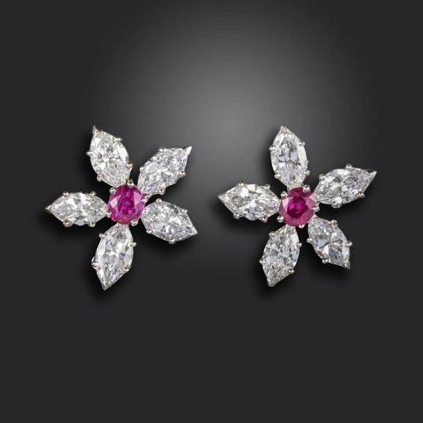 A pair of ruby and diamond flower head cluster earrings, each centred with an ov…