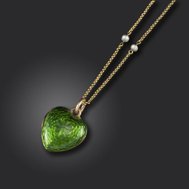 A Victorian green enamel heart shaped locket pendant, opening to reveal a glazed…