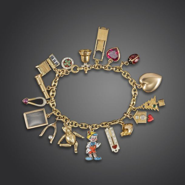 A gold anchor link bracelet mounted with sixteen gold charms, including a Cartie…