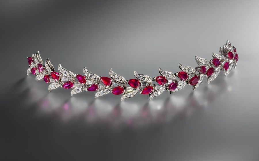 A ruby and diamond bracelet, c1960, designed as a garland of leaves, set with br…
