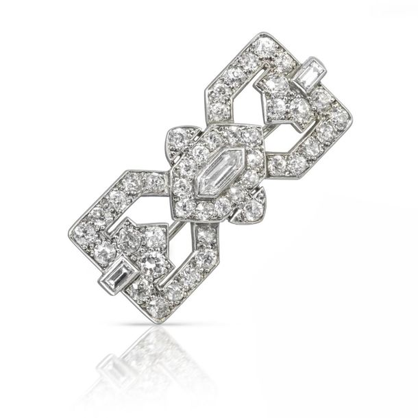 A diamond set Art Deco brooch by Cartier, centred with a lozenge shaped diamond …