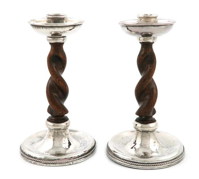 By A. E. Jones, a pair of Arts and Crafts silver and wood candlesticks, Birmingh…