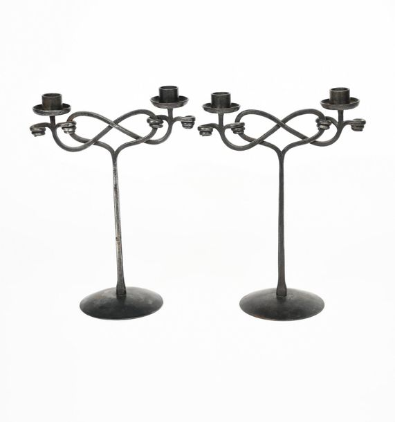 A pair of patinated wrought iron twin branch candlesticks designed by Edward Spe…