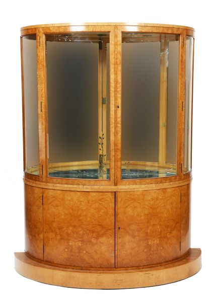 A walnut veneer bow fronted display cabinet, the curved, hinged doors with curve…