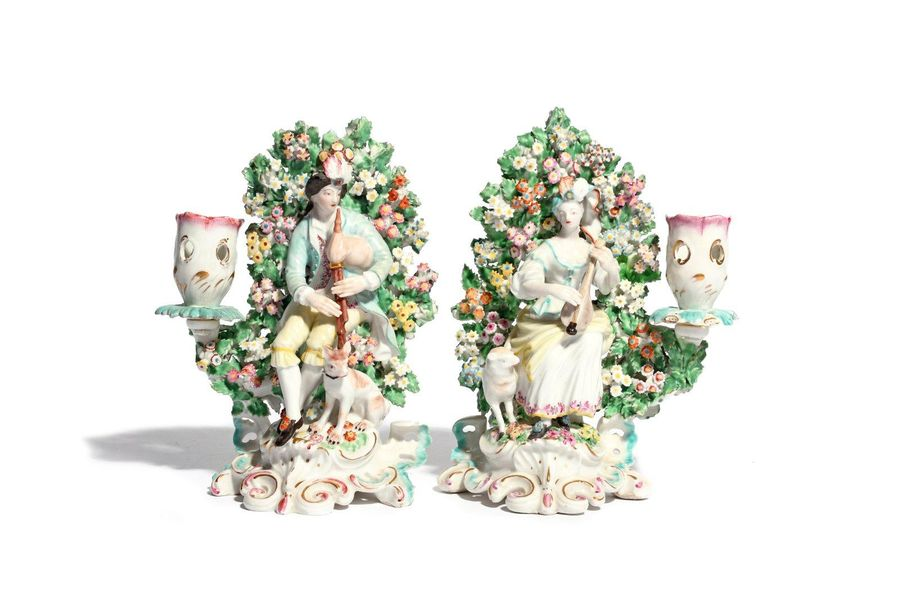 A pair of Derby figures of musical shepherds c.1760, each modelled seated before…