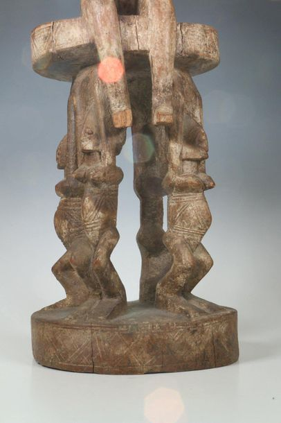 Dogon, seated female figure, on a stool carried by four standing female figures.…
